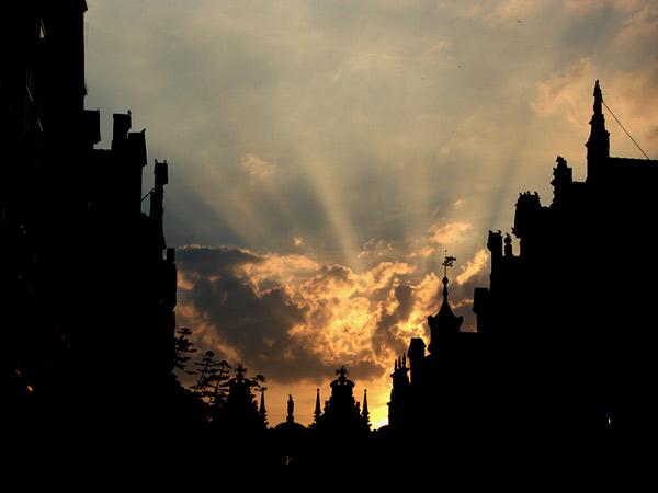 Słońce zachodzi za kamienicą
